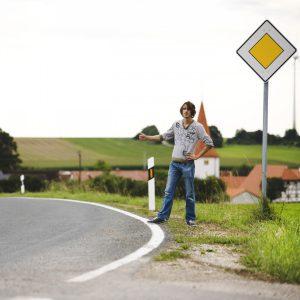 paysage herbe ciel route pelouse jouer trottoir asphalte Voyage des loisirs auto stoppeur loisir Signalisation espace public amusement Infrastructure ramasser Allemagne angle journée un jeune homme Par hitch randonnée auto-stop